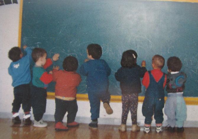 Niños y niñas de espaldas dibujando en una pizarra