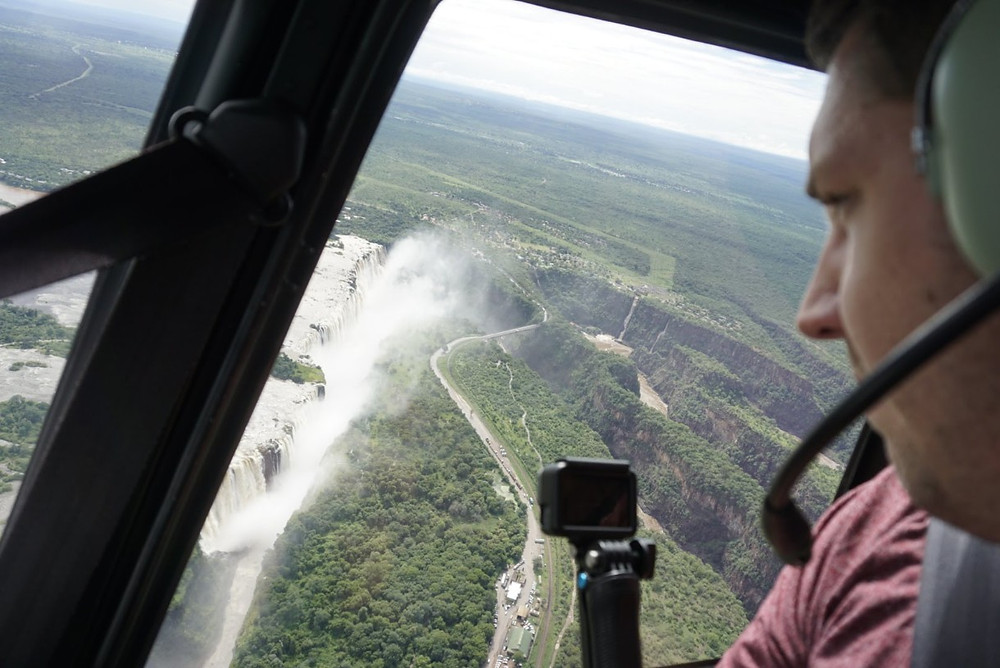 Lucas looking out helicopter over Victoria Falls