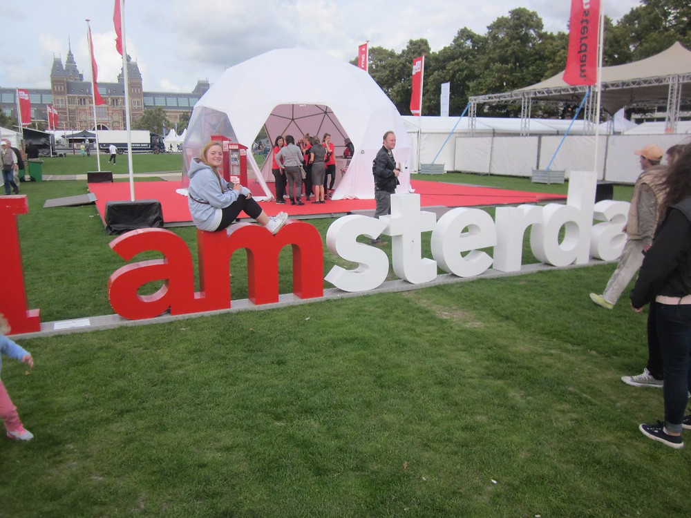 Sitting on the mini Amsterdam sign
