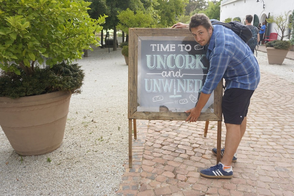"Lucas hugging wine sign ""Time to uncork and unwined"""