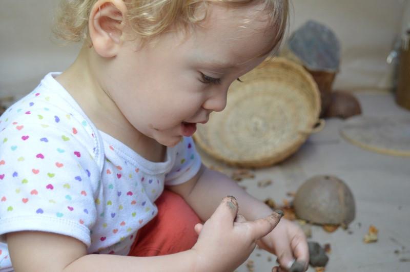 Criança explora argila