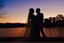 Noivos fotografam no pôr do sol.