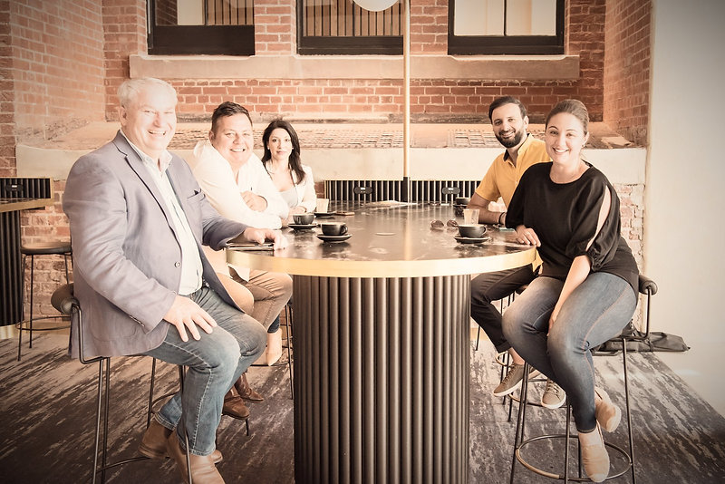 picture of Axioniq staff sitting at a high bench with coffees on the bench smiling