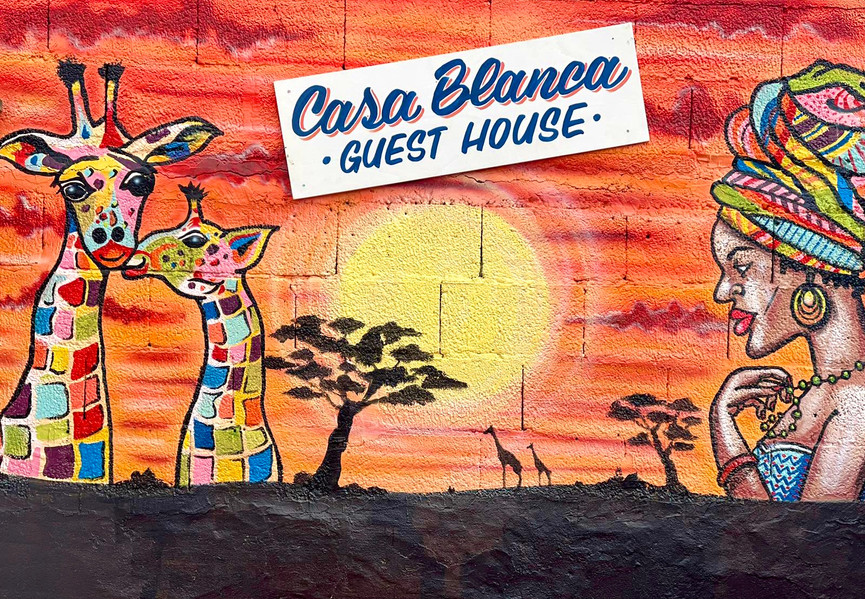 Casa Blanca Guest House Tenerife wall mural with colourful girrafes and African lady.