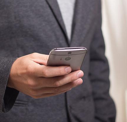 Persona en traje sujetando un teléfono móvil