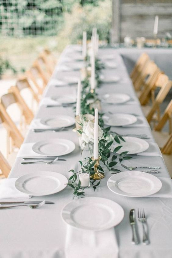 Beautiful table scape for a wedding, with simple greenery with white chargers and candles.
