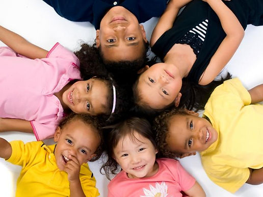 children-lying-down-in-a-circle-smiling.