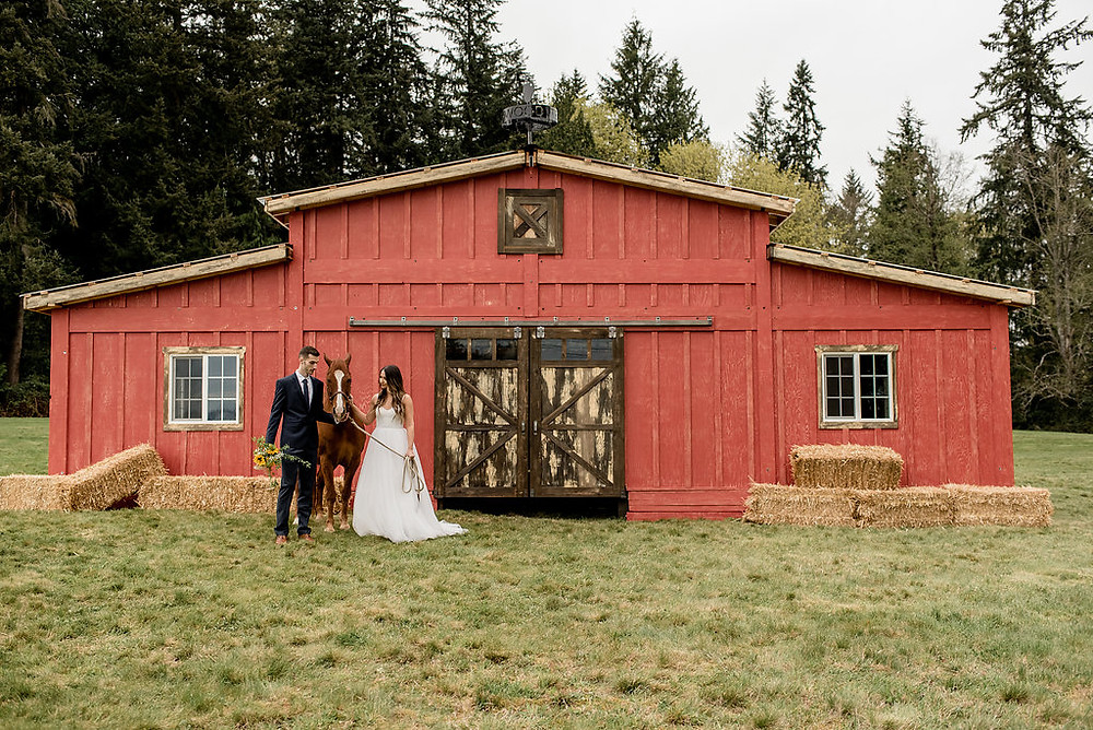 An equine-themed photo of a bride and groom in front of rustic traveling wedding venue, Tentwood barn. | My Snohomish Wedding | Snohomish Wedding Planning