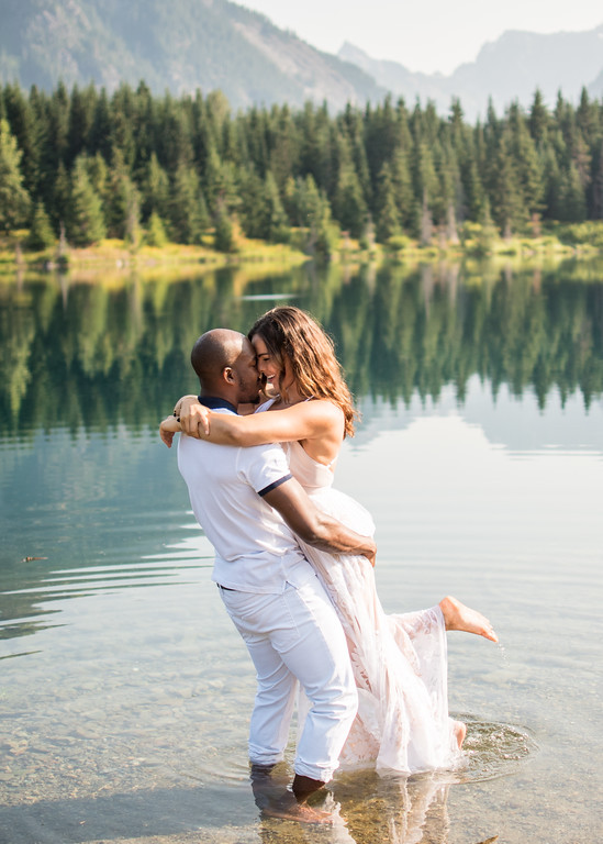An engaged couple embraces while standing in a lake during their engagement photo shoot. | My Snohomish Wedding | Wedding planning near Seattle, WA.