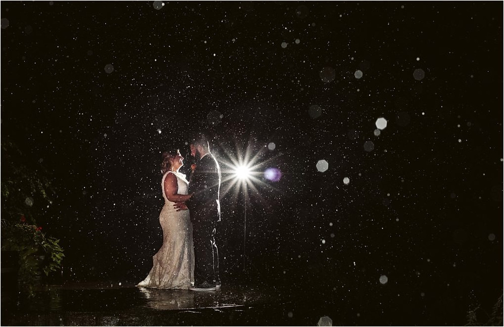 Intimate moment between couple at a rainy fall wedding at Lookout Lodge.
