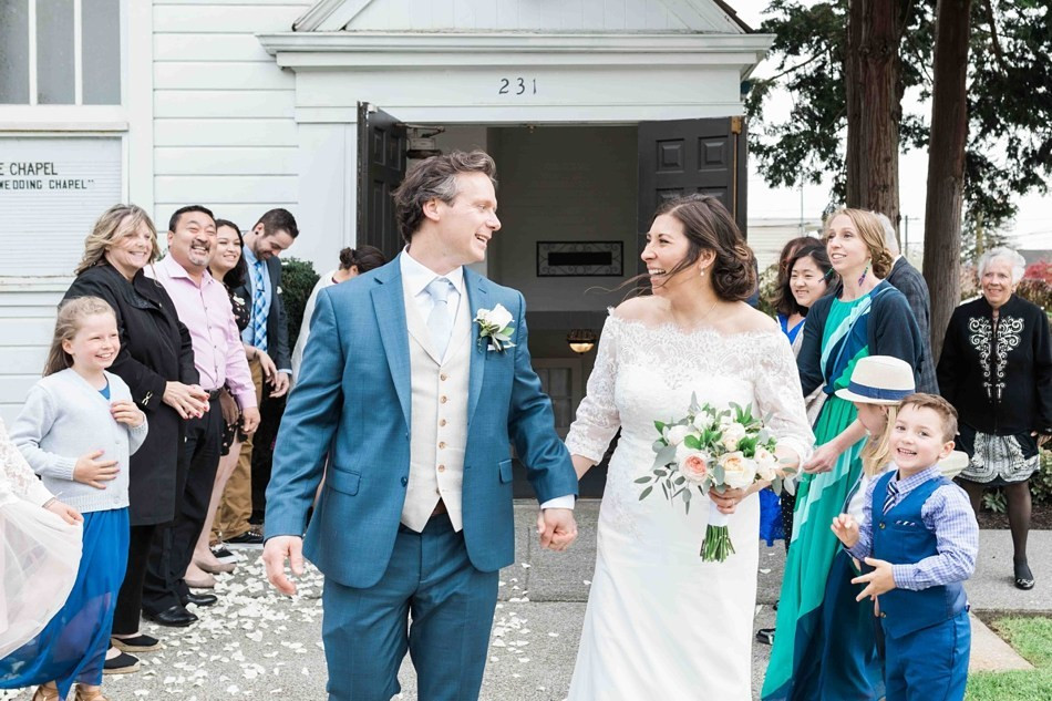 A newlywed couple holds hands as they depart their wedding ceremony at Belle Chapel, a Snohomish Wedding Venue located near Seattle, WA. | My Snohomish Wedding | Snohomish Wedding Planning