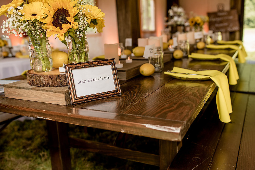 Yellow reception decorations inside rustic traveling wedding venue Tentwood barn. | My Snohomish Wedding | Snohomish Wedding Planning