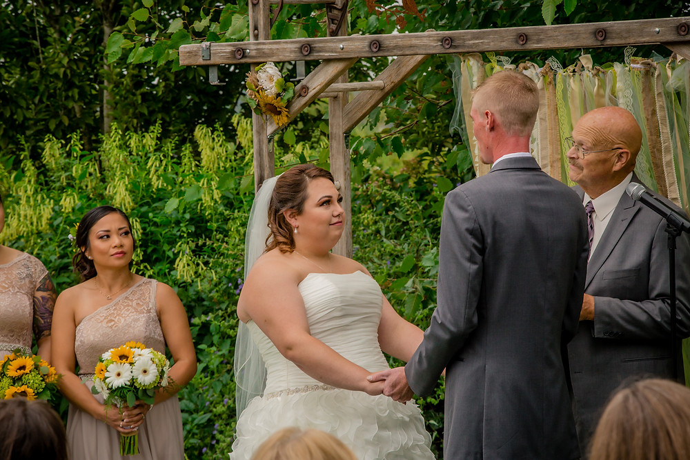 A bride and groom recite their vows during the ceremony of their wedding at the Red Barn at Stocker Farms in Snohomish, a wedding venue near Seattle, WA.
