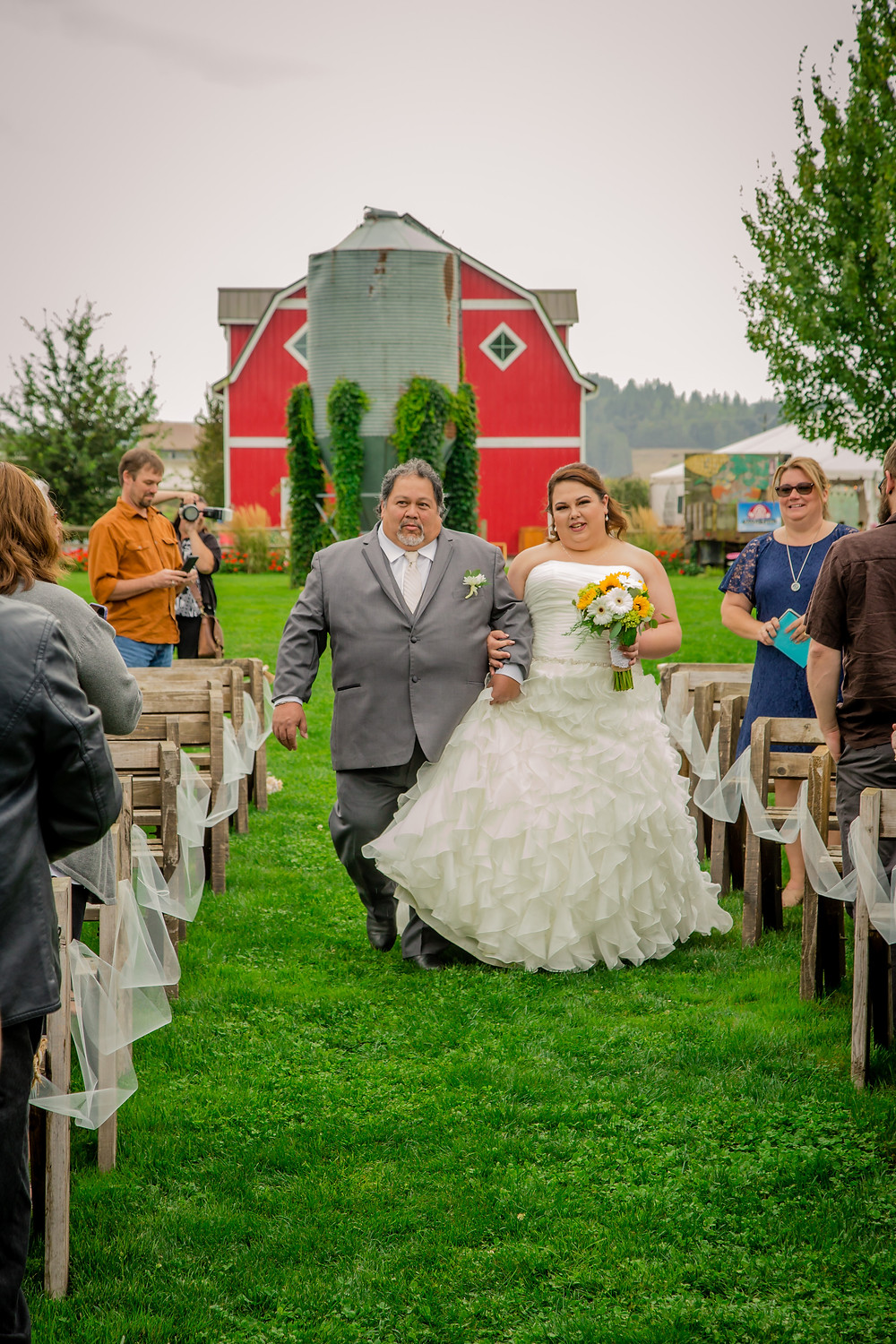 A father walks a bride down the aisle during the ceremony of her wedding at the Red Barn at Stocker Farms in Snohomish, a wedding venue near Seattle, WA.