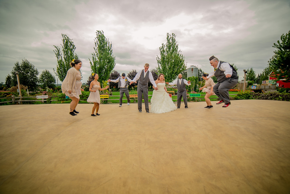 A bride, groom, and their wedding party have fun at a wedding at the Red Barn at Stocker Farms in Snohomish, a wedding venue near Seattle, WA.