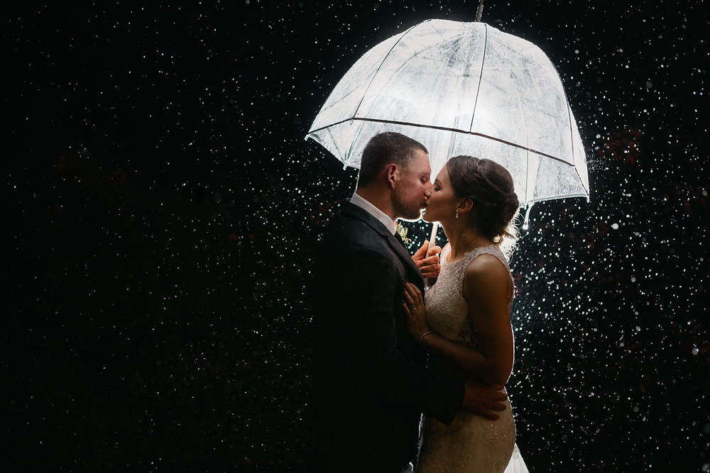 A newlywed couple kiss in the rain after their romantic, stormy wedding at Hidden Meadows in Snohomish, a wedding venue near Seattle, WA. | My Snohomish Wedding | Snohomish Wedding Planning