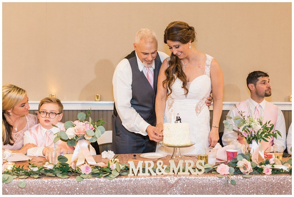 A newly married bride and groom cut their wedding cake after their wedding at Hidden Meadows in Snohomish, a wedding venue near Seattle.