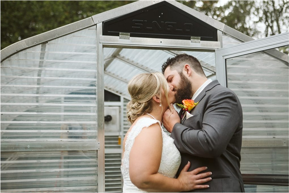 Bride and groom kiss in front of greenhouse at a rainy fall wedding at Lookout Lodge.