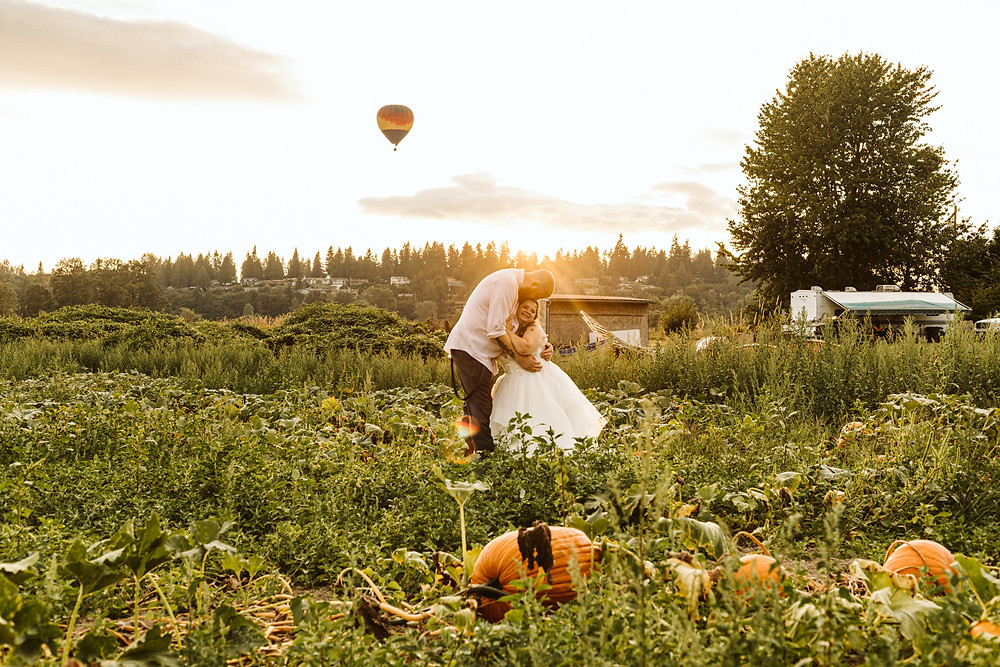 A bride and groom stand in a pumpkin patch at Craven Farms, a wedding venue in Snohomish, located near Seattle, WA. | My Snohomish Wedding | Snohomish Wedding Planning