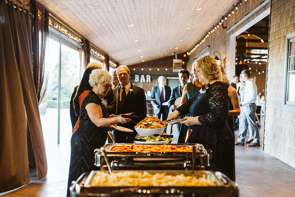 Wedding guests line up during a reception catered by The Wooden Spoon during a summer wedding at Hidden Meadows in Snohomish, a wedding venue near Seattle, WA. | My Snohomish Wedding | Snohomish Wedding Planning