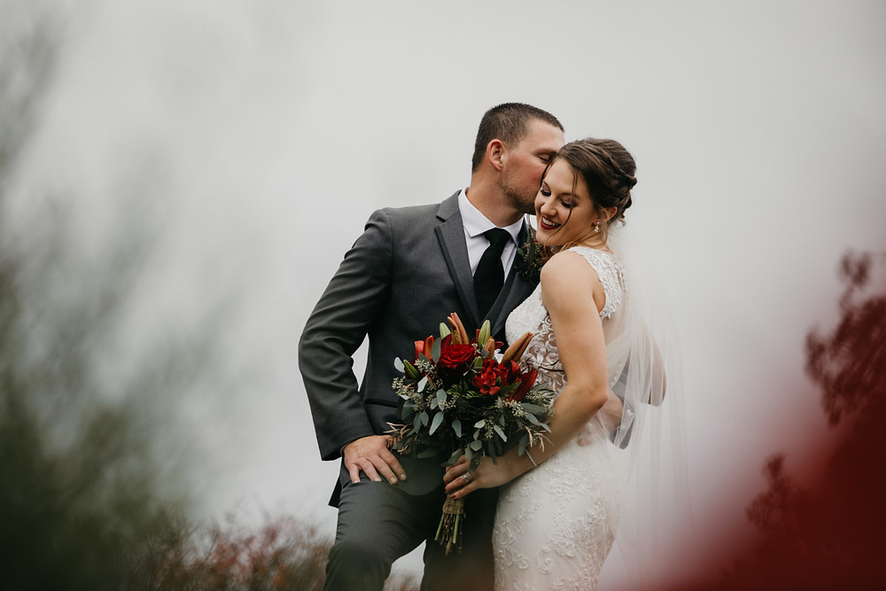 A groom kisses his bride after their romantic, stormy wedding at Hidden Meadows in Snohomish, a wedding venue near Seattle, WA. | My Snohomish Wedding | Snohomish Wedding Planning