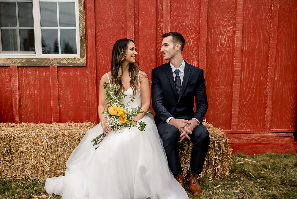 A bride and groom sit in front of rustic traveling wedding venue, Tentwood barn. | My Snohomish Wedding | Snohomish Wedding Planning