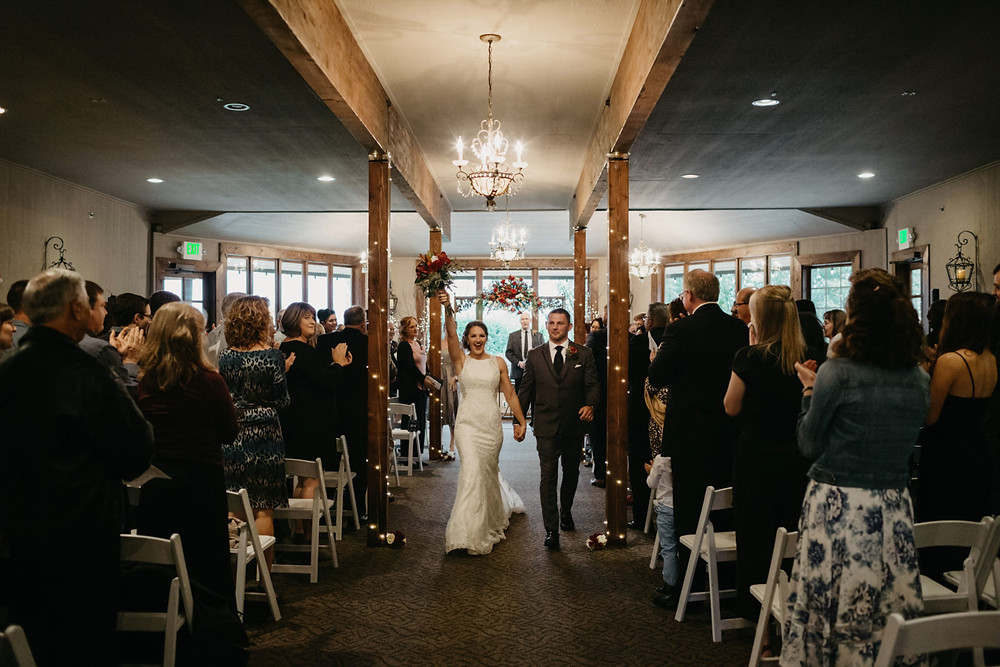 A bride and groom walk hand-in-hand after exchanging vows at their romantic, stormy wedding at Hidden Meadows in Snohomish, a wedding venue near Seattle, WA. | My Snohomish Wedding | Snohomish Wedding Planning
