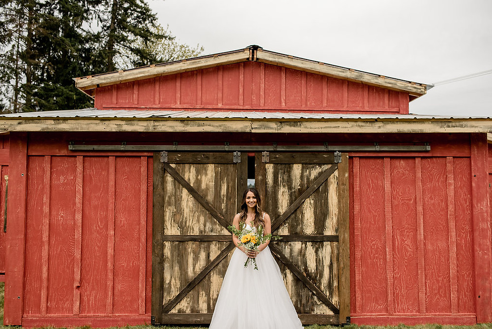 A bride stands in front of rustic traveling wedding venue, Tentwood barn. | My Snohomish Wedding | Snohomish Wedding Planning