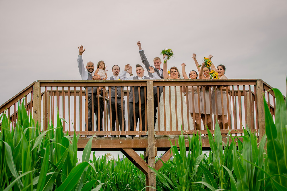 A bride, groom, and their wedding party have fun before a whimsical wedding at the Red Barn at Stocker's in Snohomish, a wedding venue near Seattle, WA.