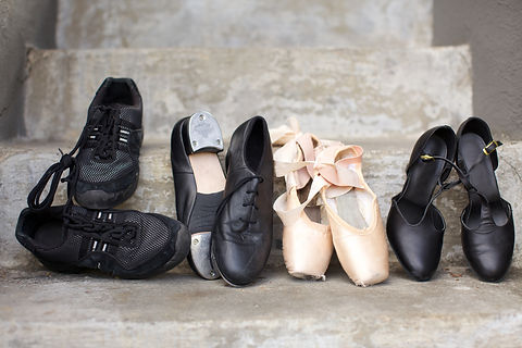 Closeup of a pair of jazz shoes, tap shoes, ballet pointe shoes, and character shoes representing a