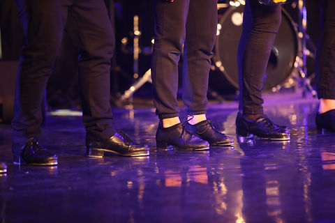 A group of tap-dancers in black leather