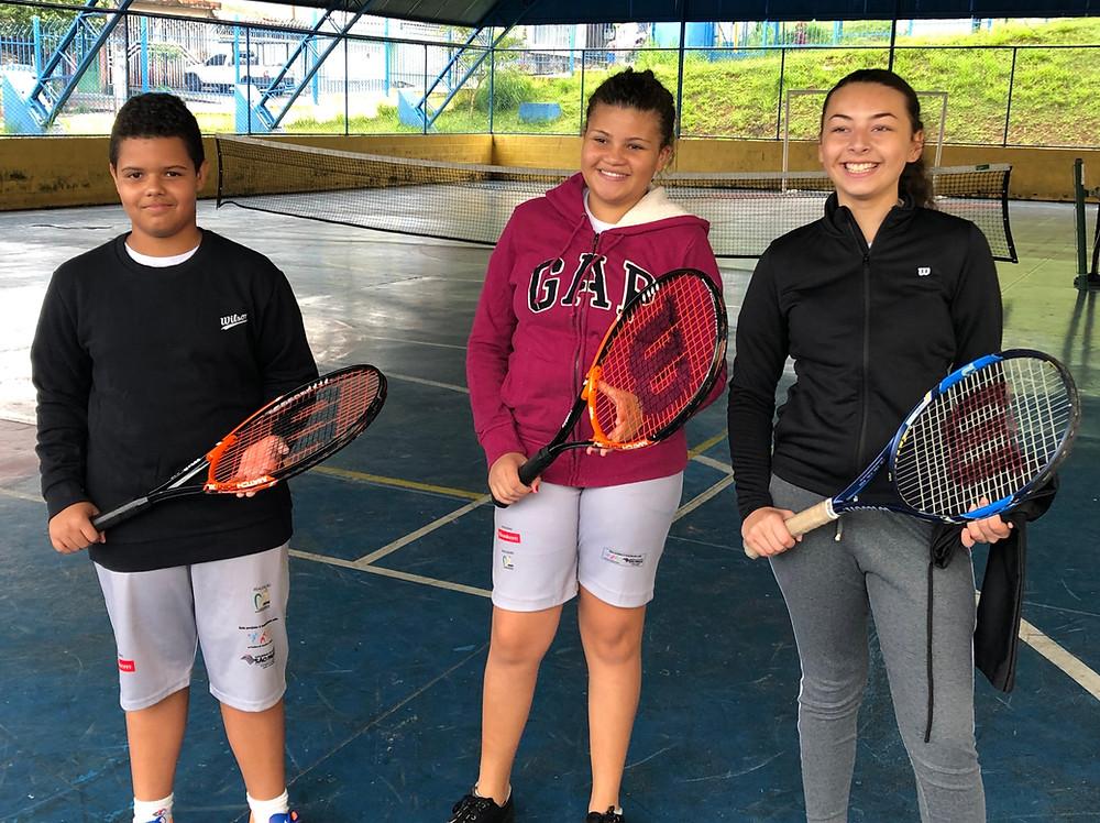 Da esquerda para a direita: Walace, Giovana e Gabriela, exibindo as raquetes que ganharam do projeto.
