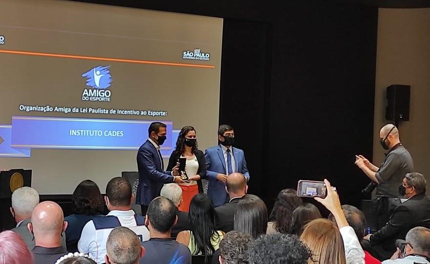 Governador João Doria entregando prêmio para a presidente do Instituto Cades.