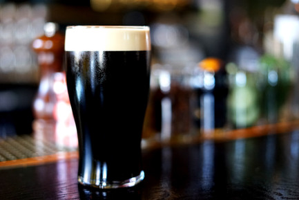 A dark beer in a pint glass on The Stalking Horse's bar