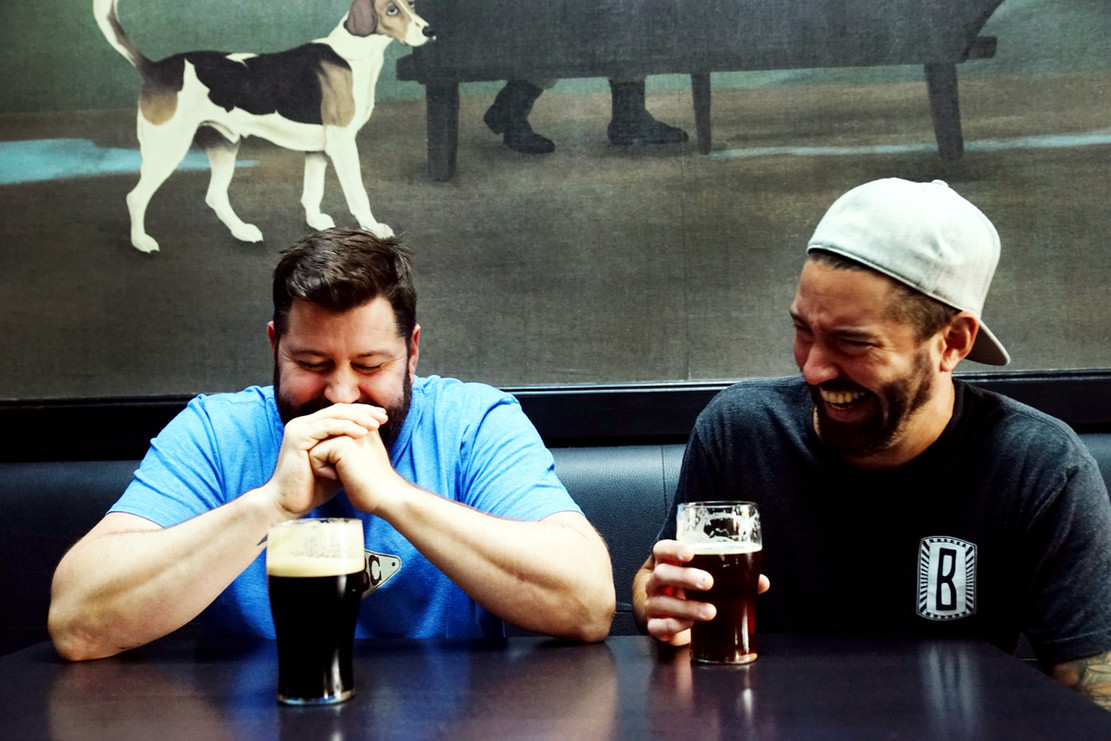 Brewers Brandon Edwards and Noah Regnery, laughing in front of The Stalking Horse mural