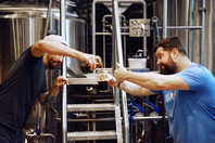 Brewers Noah Regnery and Brandon Edwards playfully pouring beer by Brite tanks