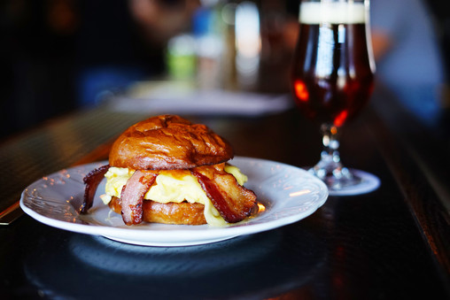 The breakfast sandwich and a goblet of dark beer
