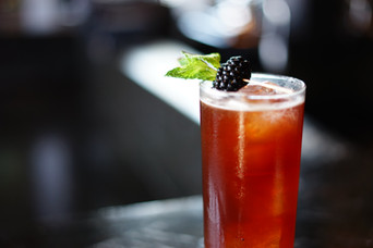 A blackberry cocktail in a Collins glass