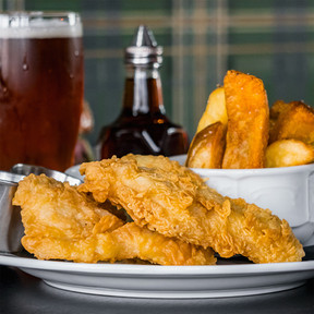 A plate of fish n chips, an amber beer, and malt vinegar
