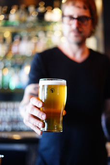 A Stalking Horse bartender holding out a pint of light beer