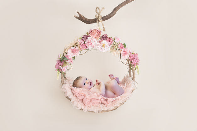 Newborn baby in pink floral wreath
