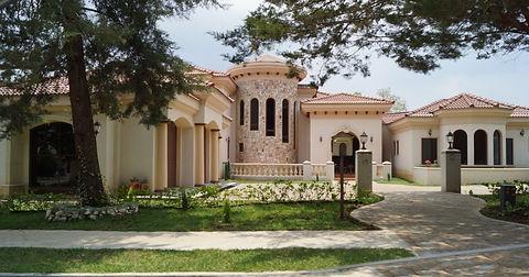Casa de lujo con detalle de piedra, techo de teja y columnas