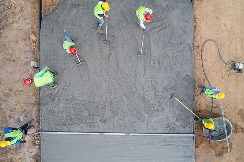 A construction worker pouring a wet conc