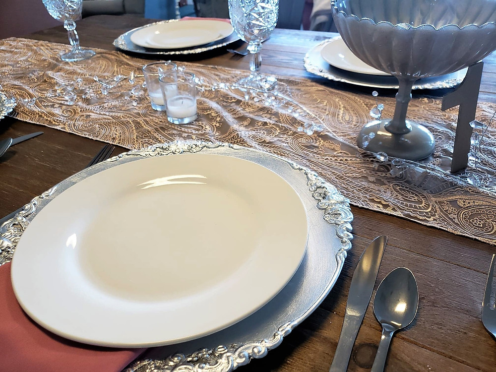 Mauve linen napkins, silver vintage charger plates, champagne paisley lace runner and a silver glass compote round out the scene.