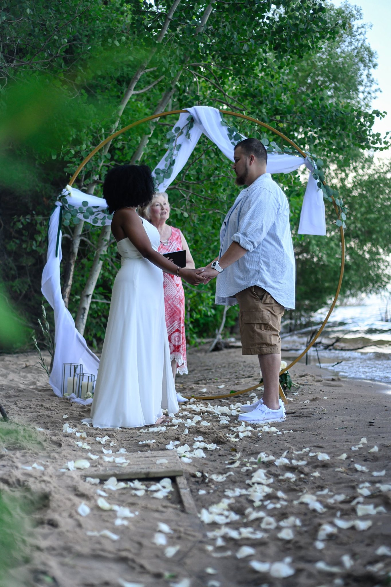 vows in front of circle arch beach