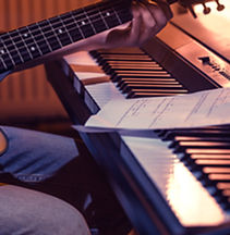 man-playing-acoustic-guitar-and-piano-cl