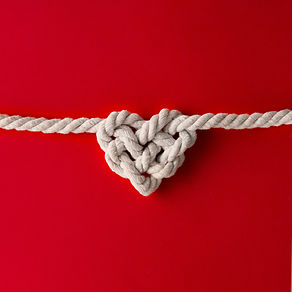White rope in heart shape knot on red ba