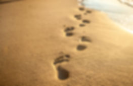 Footprints at sunset with golden sand. b