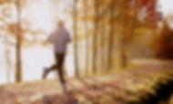 Man running in park at autumn morning. H