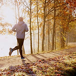 Man running in park at autumn morning. H